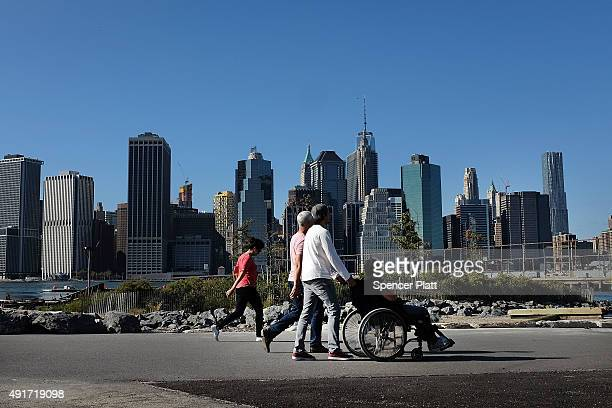 People walk the warm early autumn weather on October 7 2015 in Brooklyn borough of New York City Temperatures are predicted to stay in the sixties...