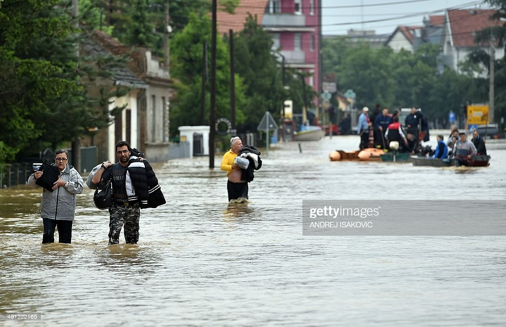 People walk throug a flooded street in Obrenovac 40 kilometers west of Belgrade on May 16 2014 Three people have drowned in Serbia and over 6000 have...
