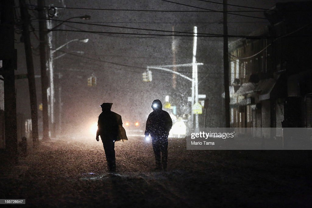 People walk through a darkened street using flashlights as a police spotlight shines behind them during a Nor'Easter snowstorm in the Rockaway neighborhood on November 7, 2012 in the Queens borough of New York City. The Rockaway Peninsula was especially hard hit by Superstorm Sandy and some are evacuating ahead of the coming storm.