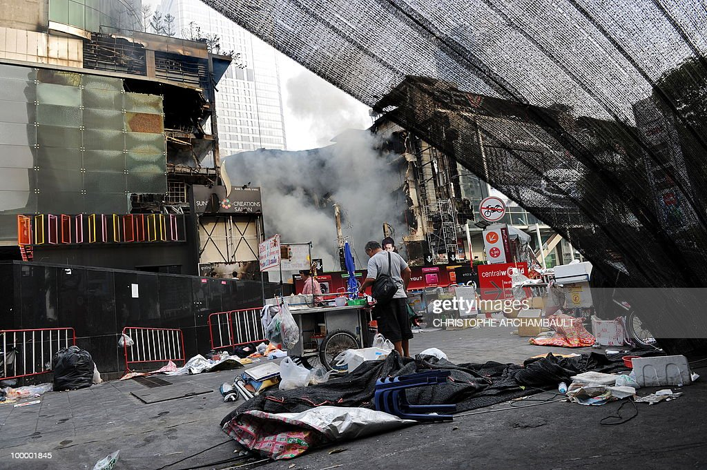 People walk through a dismantled anti-government protest zone as Thailand's biggest shopping mall - Central World - keeps burning after it was set ablaze the day before following an army assault, in downtown Bangkok on May 20, 2010. Plumes of smoke hung overhead and gunfire crackled as Bangkok emerged from an curfew aimed at quelling mayhem unleashed by enraged anti-government protesters targeted in an army offensive. AFP PHOTO/Christophe ARCHAMBAULT