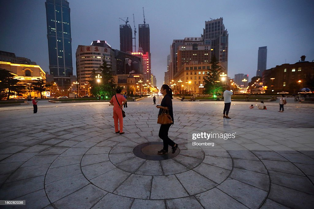 People walk through a park as buildings stand in the background at night in Dalian in Dalian China on Tuesday Sept 10 2013 Goldman Sachs Group Inc...