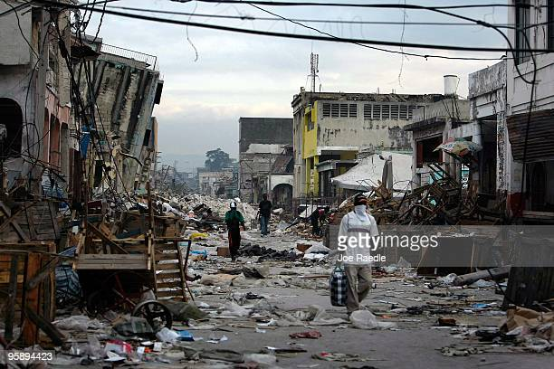 People walk through a street where destroyed buildings are seen after the massive earthquake struck January 20 2010 in PortauPrince Haiti Planeloads...