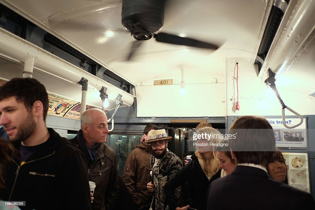 People walk through a vintage New York City subway car as it moves along the M line on December 16, 2012 in New York City. The New York Metropolitan Transportation Authority (MTA) runs vintage subway trains from the 1930's-1970's each Sunday along the M train route from Manhattan to Queens through the first of the year.