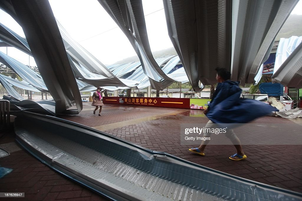 People walk through an advertising billboard damaged by strong winds on November 10, 2013 in Sanya, China. Typhoon Haiyan, now a tropical depression, brought strong winds and rainstorms to South China on Sunday.
