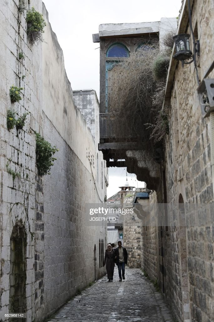 People walk through an alley in the old city of Hama, in central Syria, on March 13, 2017