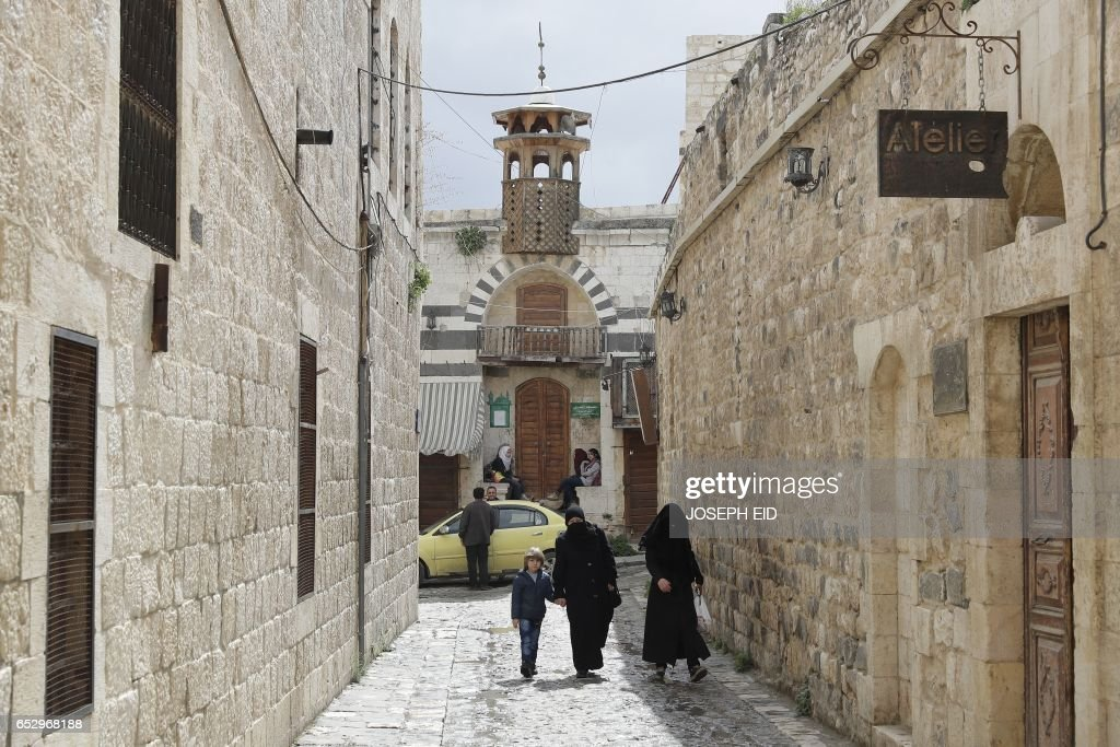 People walk through an alley in the old city of Hama, in central Syria, on March 13, 2017. /