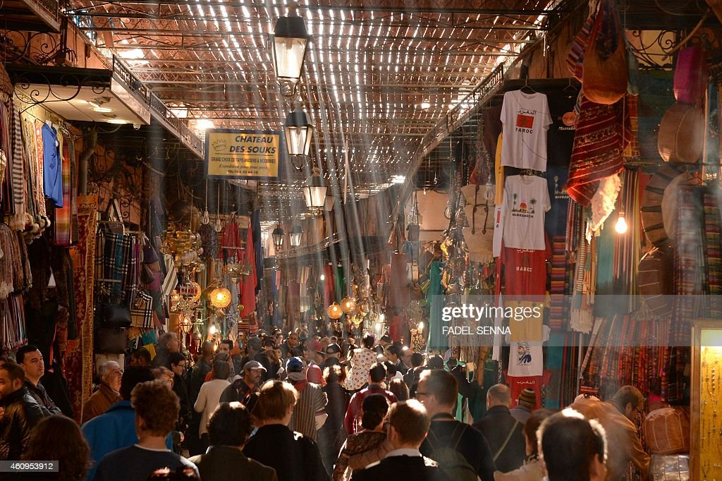 People walk through an alley of a traditional souk in the old Medina of Marrakesh on December 30 2014 AFP PHOTO /FADEL SENNA
