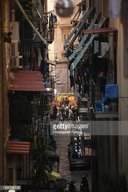 People walk through an alleyway of densely populated Naples on November 18 2011 in Naples Italy Italy's new Prime Minister Mario Monti and his new...