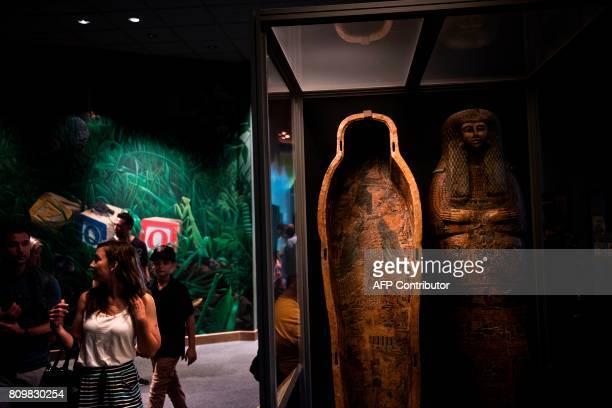 People walk through an exhibit on mummies at the Smithsonian's Natural History Museum on July 6 2017 in Washington DC / AFP PHOTO / Brendan Smialowski