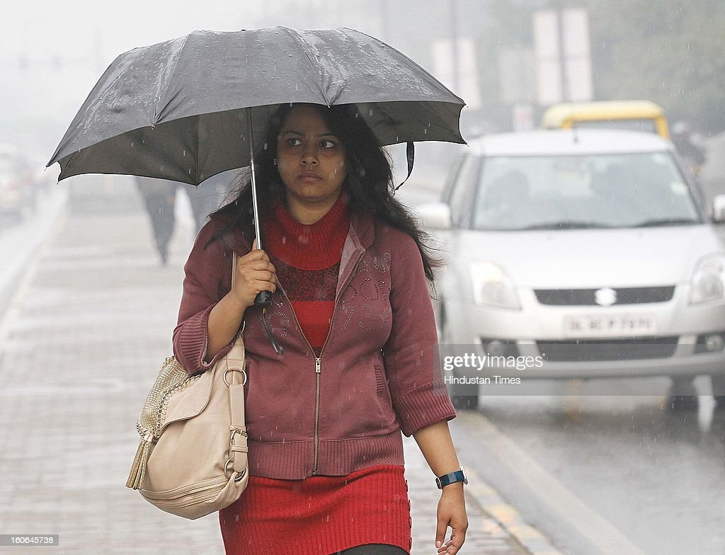 People walk through Barakhamba road as it rains in morning hours in national capital, on February 4, 2013 in New Delhi, India. MeT Office has predicted that the capital is likely to experience hailstorms and rains in some parts.