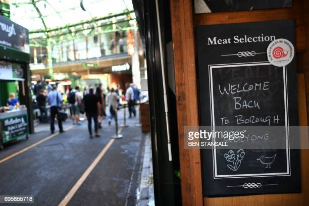 People walk through Borough Market in central London following its reopening after the June 3 terror attack on June 14 2017 Three assailants were...