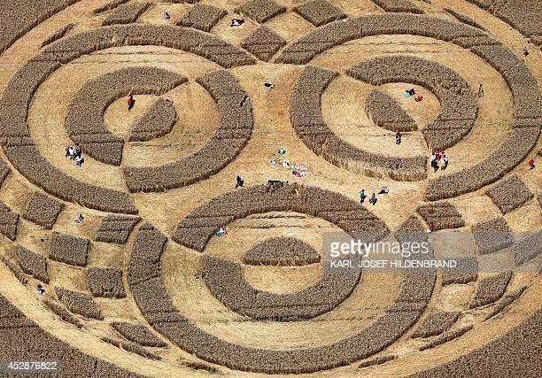 People walk through crop circles shaped into a cornfield near Raisting southern Germany on July 28 2014 According to media reports a balloonist had...