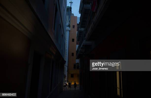 People walk through darkened streets on October 1 2017 in Old San Juan Puerto Rico Hurricane Maria caused extensive damage to the island as residents...