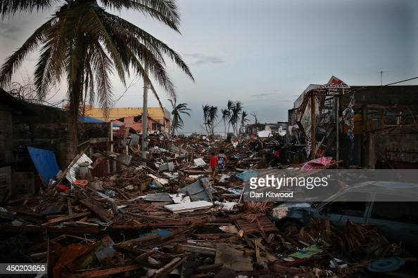 People walk through debris in a particularly badly damaged area of town near the Cathedral of Our Lord's Transfiguration Parish Palo church which has...