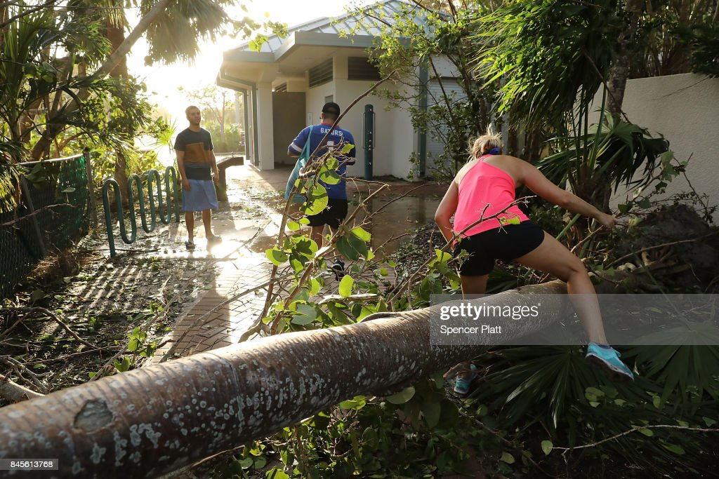People walk through downed trees the morning after Hurricane Irma swept through the area on September 11, 2017 in Fort Myers, Florida. Hurricane Irma made another landfall near Naples yesterday after inundating the Florida Keys. Electricity was out in much of the region with localized flooding.