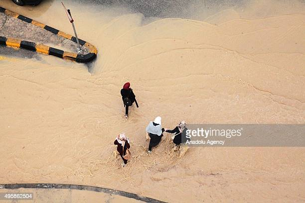 People walk through flooded street following heavy rains in Amman Jordan on 05 November 2015
