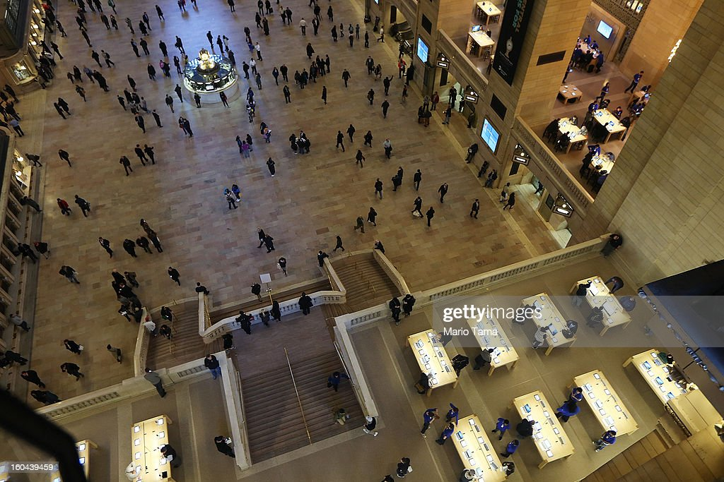 People walk through Grand Central Terminal as others (Bottom) gather in the Apple store on the day before the famed Manhattan transit hub turns 100 years old on January 31, 2013 in New York City. The terminal opened in 1913 and is the world's largest terminal covering 49 acres with 33 miles of track. Each day 700,000 people pass through the terminal where Metro-North Railroad operates 700 trains per day.