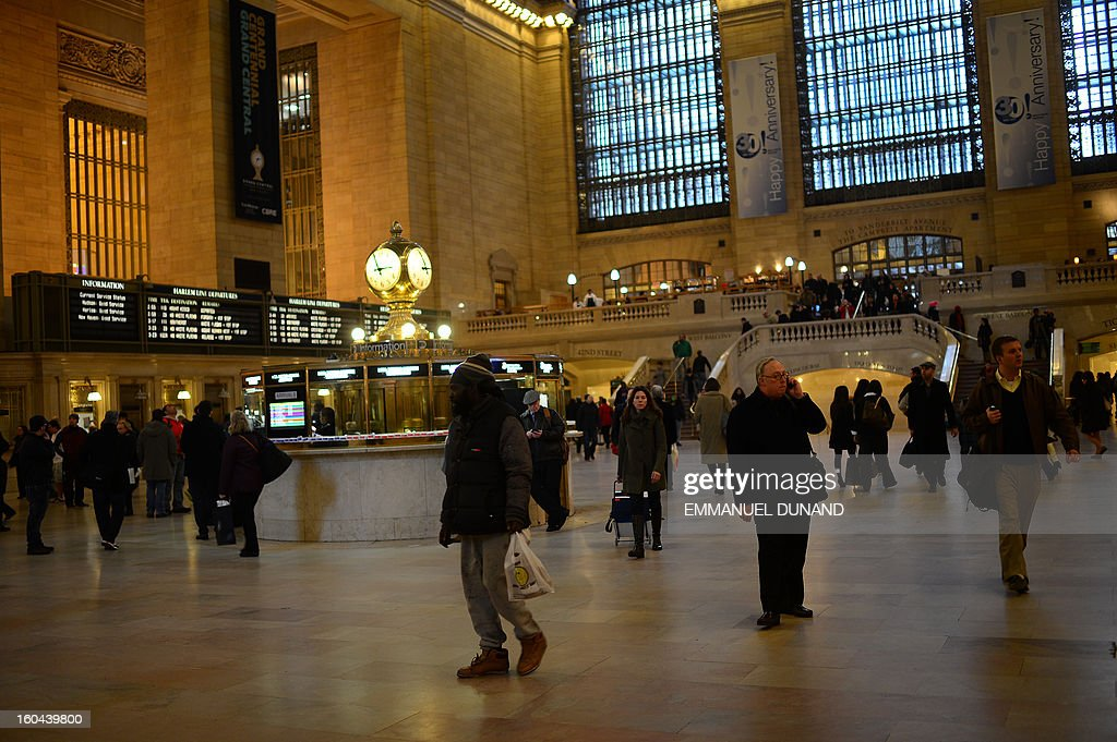 People walk through Grand Central Terminal in New York, January 29 , 2013. Grand Central, the doyenne of US train stations, is celebrating its 100th birthday on February 2, 2013. Opened when trains were a luxurious means of traveling across The US, the New York landmark, with its Beaux-Arts facade, is still one of the US largest transportation hubs and is also New York's second-most-popular tourist attraction, after Times Square. AFP PHOTO/Emmanuel Dunand