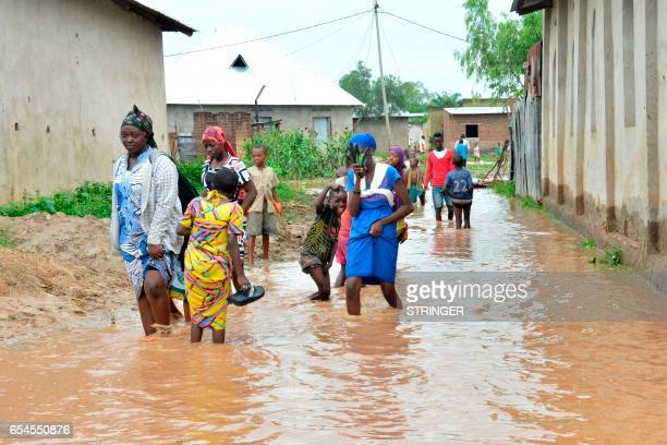 People walk through polluted floodwaters in Buterere northwest of Bujumbura on March 17 after overnight torrential rains destroyed more than 100...