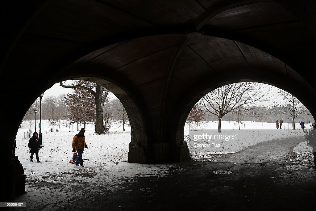 People walk through Prospect Park during a snow storm on December 14, 2013 in the Brooklyn borough of New York City. Much of the Northeast was hit by a storm stretching over 1,000 miles that could result in at least a foot of snow on parts of New England.