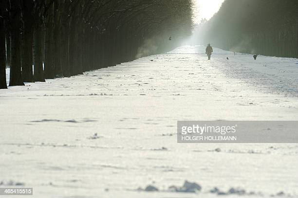 People walk through snow at the Herrenhausen Gardens in Hanover Germany on January 27 2014 AFP PHOTO / DPA / GERMANY OOUT HOLGER HOLLEMANN