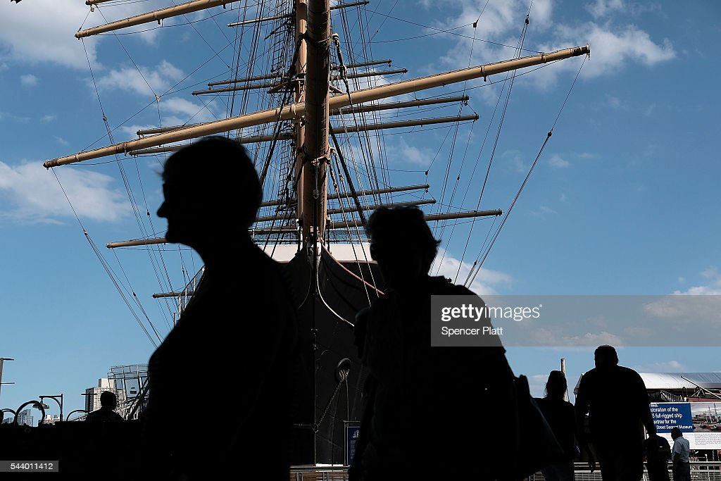 People walk through South Street Seaport in lower Manhattan on a warm June evening on June 30, 2016 in New York City. New York City residents and thousands of tourists are preparing for the Fourth of July weekend which is expected to be warm and sunny.