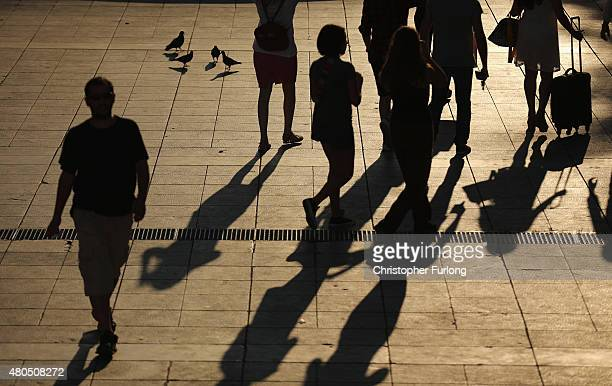 People walk through Syntagma Square as antiausterity demonstrators gather in front of the Greek parliament whilst Eurozone leaders in Brussels...