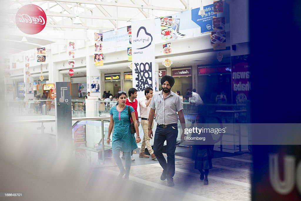 People walk through the AlphaOne shopping mall in Amritsar, India, on Thursday, May 9, 2013. India's consumer price index (CPI) for April rose 9.39 percent year on year, the Central Statistics Office said in a statement on its website. Photographer: Brent Lewin/Bloomberg via Getty Images