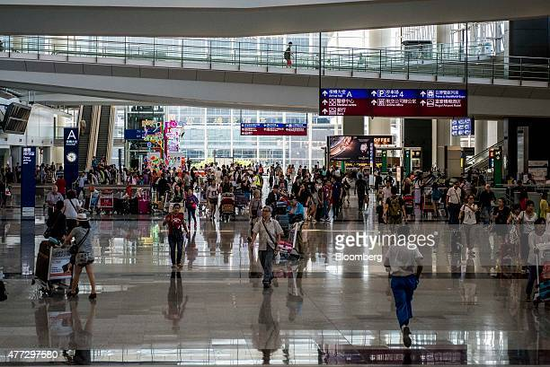 People walk through the arrivals hall at Hong Kong International Airport in Hong Kong China on Monday June 15 2015 The Hong Kong government in March...