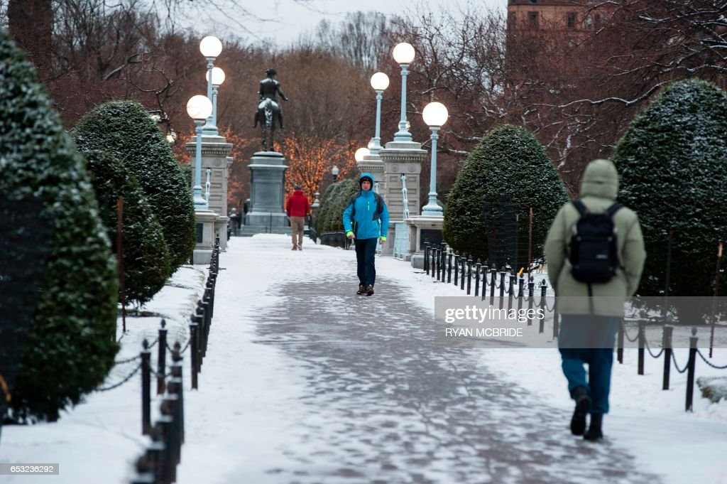 People walk through the Boston Garden March 14, 2017 in Boston, Massachusetts. Winter Storm Stella dumped snow and sleet Tuesday across the northeastern United States where thousands of flights were canceled and schools closed, but appeared less severe than initially forecast. PHOTO / Ryan McBride