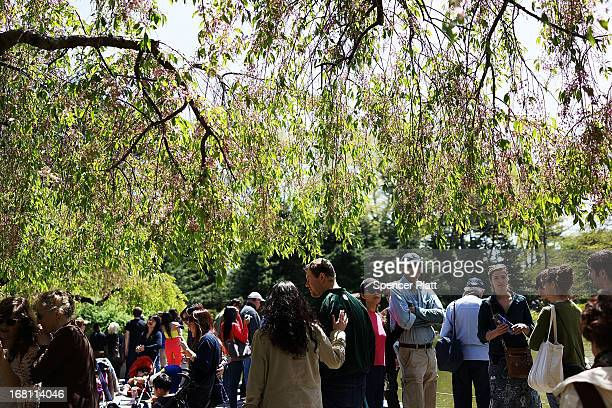 People walk through the Brooklyn Botanical Garden on May 5 2013 in New York City The botanical garden which sits on 52acres features numerous gardens...