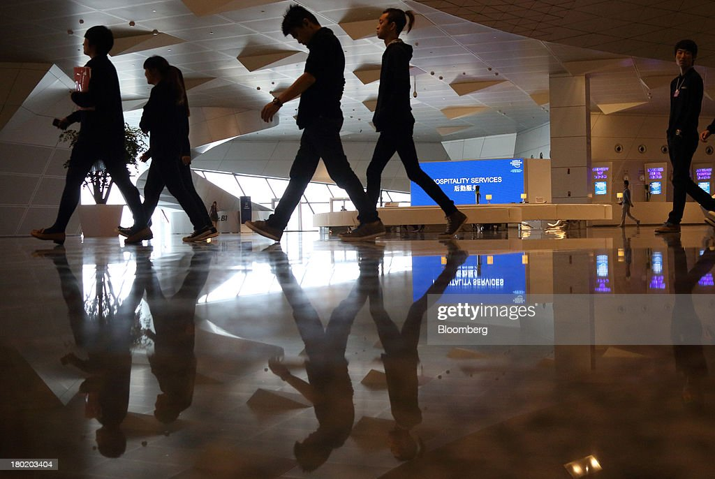 People walk through the Dalian International Conference Center in Dalian, China, on Tuesday, Sept. 10, 2013. The World Economic Forum Annual Meeting Of The New Champions 2013 will be held in Dalian from Sept. 11 to 13. Photographer: Tomohiro Ohsumi/Bloomberg via Getty Images