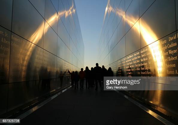 People walk through the Empty Sky 9/11 memorial at sunset in Liberty State Park on January 1 2017 in Jersey City NJ