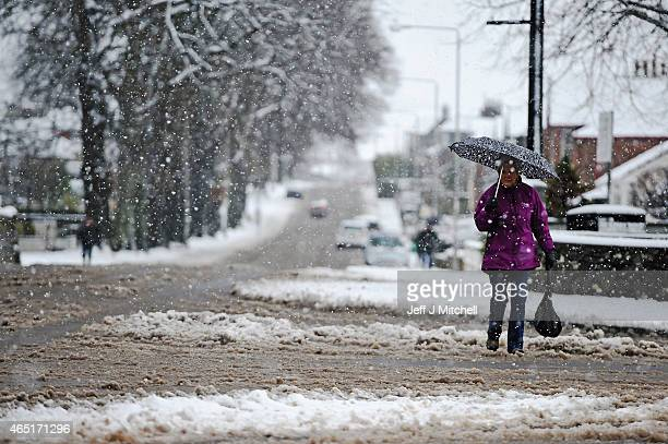 People walk through the falling snow as it prompts closure of a number of schools while affecting driving conditions on March 3 2015 in Balloch...