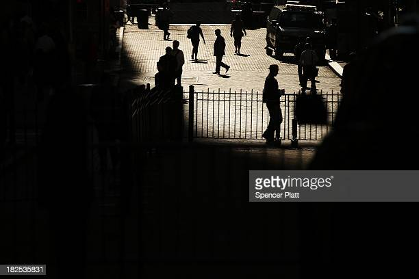 People walk through the financial district near the New York Stock Exchange during morning trading on September 30 2013 in New York City As a US...