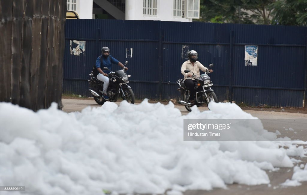 People walk through the flying froth from the polluted Bellandur Lake on August 17, 2017 in Bengaluru, India. Rapid urbanisation is taking its toll, between 2001 and 2011, the city's population increased from 6.5 million to 9.6 million, the highest rate of growth of any city in India. The indiscriminate discharge of household waste and industrial effluents into lakes is what causes the toxicity, leading to the water body foaming. According to a report by the Karnataka State Pollution Control Board, of the 67 lakes surveyed in Bengaluru, none had water that was fit for drinking.