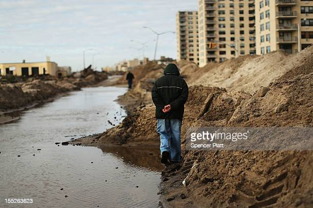 People walk through the heavily damaged Rockaway neighborhood in Queens where a large section of the iconic boardwalk was washed away on November 2...