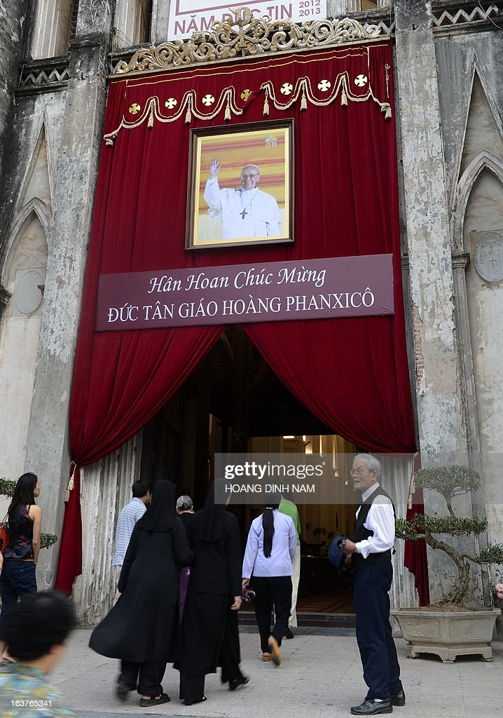 People walk through the main gate of Hanoi's cathedral with a portrait of the newly elected Pope Francis and a banner reading 'Joyfully welcoming Pope Francis' as they attend the Friday Mass on March 15, 2013. With about 6 million followers, the communist nation's Catholic community ranks second in the number of catholics after the Philippines in Southeast Asia. AFP PHOTO/HOANG DINH Nam
