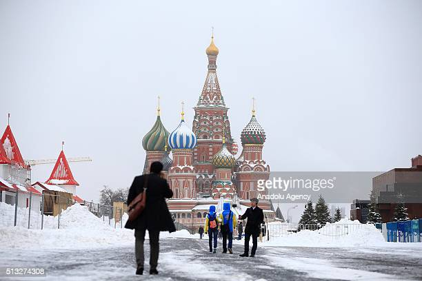 People walk through the Red Square following a snowfall in Moscow Russia on March 02 2016