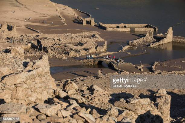 People walk through the remains of the former town of Mansilla on October 8 2016 after the village emerged from the depths of the Mansilla Reservoir...
