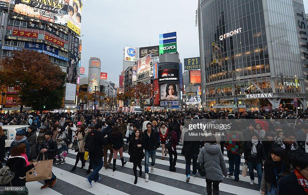 People walk through the Shibuya crossing on December 2, 2012 in Tokyo, Japan.