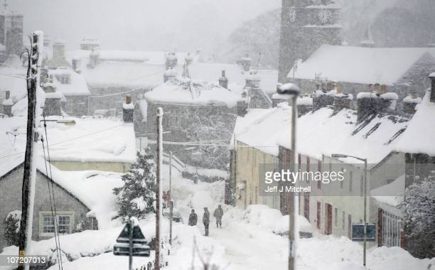 People walk through the snow on November 30 2010 in Dunning Scotland United Kingdom Freezing weather conditions and snow that has created chaos in...