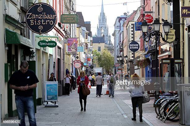 People walk through the streets in Cork city centre southern Ireland on October 2 2014 Perched on top of a hill overlooking the Irish city of Cork...
