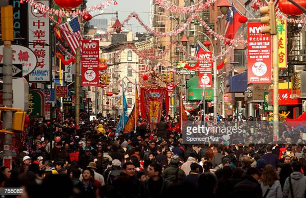 People walk through the streets of New York's Chinatown February 12 2002 on the first day of the Chinese Lunar New Year Thousands of Chinese...