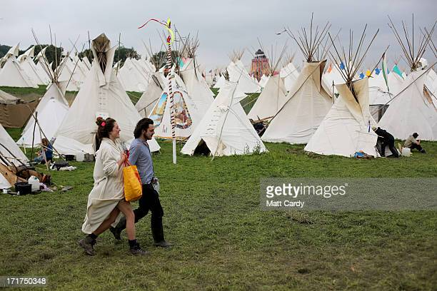 People walk through the tipi field at the Glastonbury Festival of Contemporary Performing Arts site at Worthy Farm Pilton on June 28 2013 near...