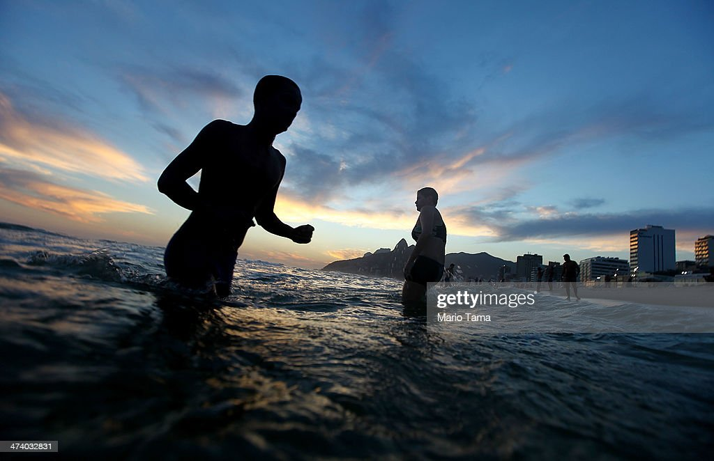 People walk through the water on Ipanema Beach on February 21, 2014 in Rio de Janeiro, Brazil. Brazil is ramping up to host the 2014 FIFA World Cup and the Rio 2016 Olympic Games.