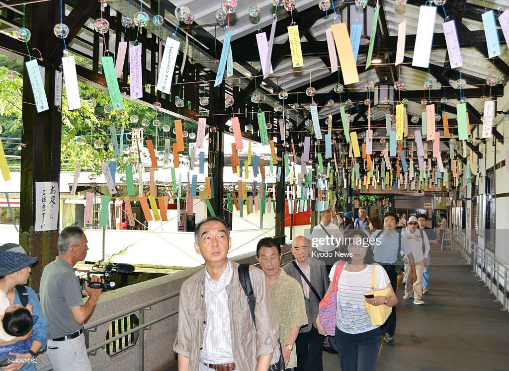 People walk through the 'wind bell tunnel' at the Gokurakubashi Station of Nankai Electric Railway Co. in the western Japan town of Koya on July 1, 2016. The installation with around 550 glass wind bells has been a feature there every summer since 2013 to entertain tourists who visit Mt. Koya, a World Heritage site, by cable car from the station.