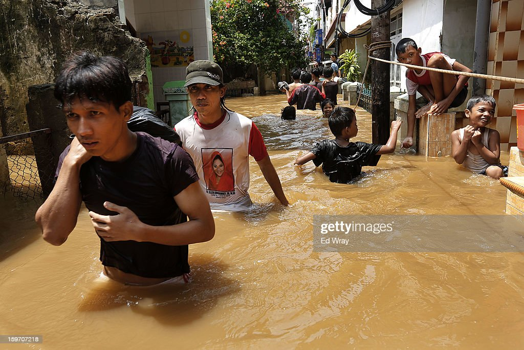 People walk through their flooded neighborhood after floodwaters receded enough for them to visit their homes on January 19, 2013 in Jakarta, Indonesia. Floodwaters receded today after three days of heavy flooding which left thousands of people's homes underwater. According to Indonesian police the death toll has reached 15.
