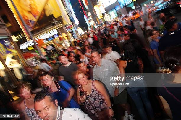 People walk through Times Square on August 19 2015 in New York City As the iconic Times Square continues to draw tourists with its entertaining and...