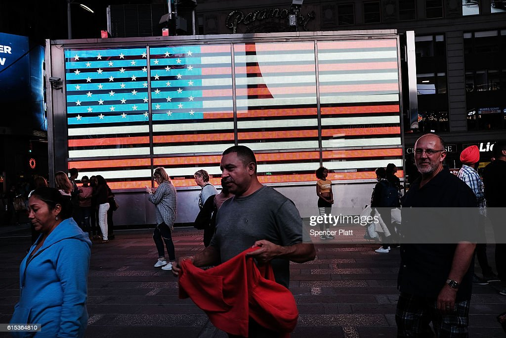 People walk through Times Square on October 17, 2016 in New York City. As the nation prepares for the final debate between presidential candidates Donald Trump and Hillary Clinton, America has become transfixed on the issues surrounding the two historic candidates. America will go to the poles to pick the next president on November 8.